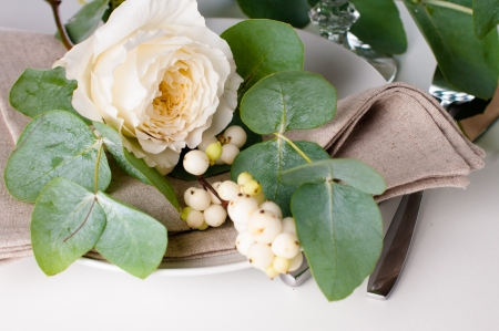 Festive table setting with floral decoration, white roses, leaves and berries on a white background Stock Photo - 22278312