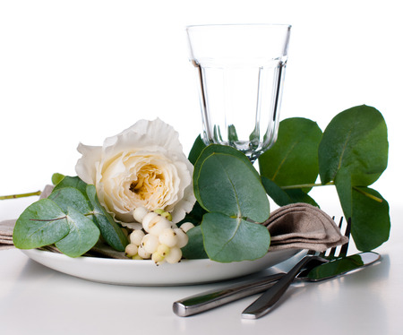 Festive table setting with floral decoration, white roses, leaves and berries on a white background Stock Photo - 22278313