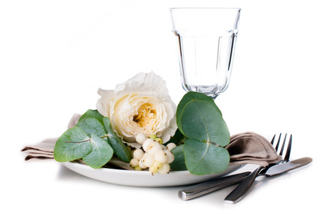Festive table setting with floral decoration, white roses, leaves and berries on a white background Stock Photo - 22278314