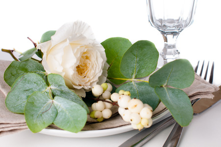 Festive table setting with floral decoration, white roses, leaves and berries on a white background Stock Photo - 22278315