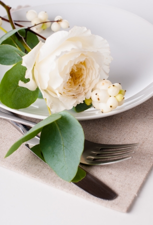 Festive table setting with floral decoration, white roses, leaves and berries on a white background photo