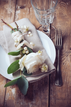 Vintage table setting with floral decorations, napkins, white roses, leaves and berries on a wooden board background Stock Photo - 22278347