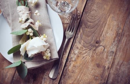 葉し、木の板の背景に漿果を花の装飾、ナプキン、白バラとビンテージ テーブルの設定