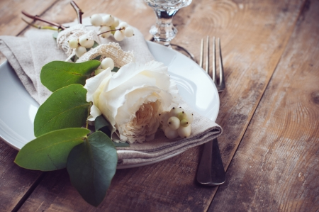 Vintage table setting with floral decorations, napkins, white roses, leaves and berries on a wooden board background Stock Photo - 22278352