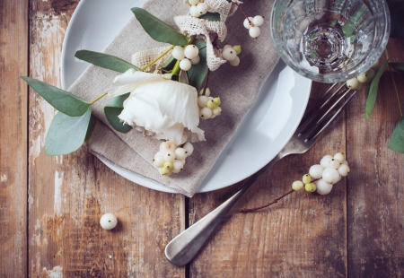 Vintage table setting with floral decorations, napkins, white roses, leaves and berries on a wooden board background