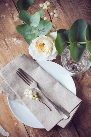 wedding table setting: Vintage table setting with floral decorations, napkins, white roses, leaves and berries on a wooden board background