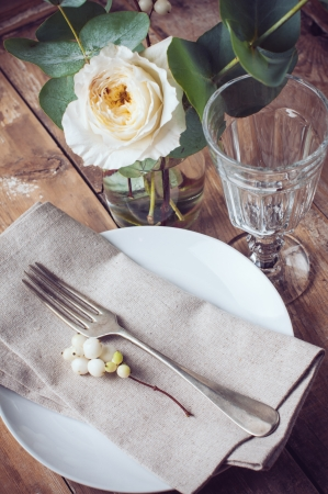 Vintage table setting with floral decorations, napkins, white roses, leaves and berries on a wooden board background Stock Photo - 22278357