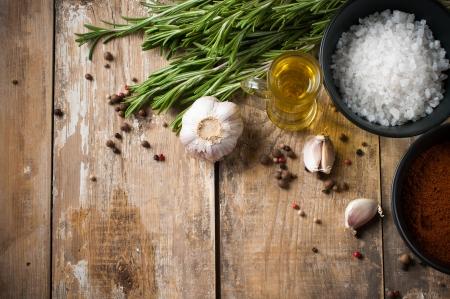 さまざまなスパイス、ローズマリー、オール スパイス、ニンニク オイルと木の板、素朴なキッチンの背景に塩