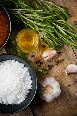 Different spices, rosemary, allspice, garlic, oil and salt on a wooden board, rustic kitchen background photo