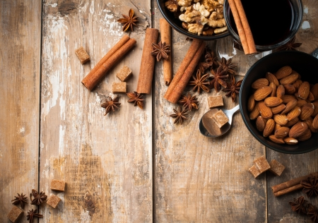 brown sugar: A glass of hot mulled wine, spices, cinnamon, star anise, brown sugar and nuts on a wooden board