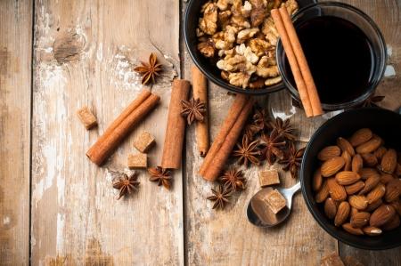 Ein Glas Glühwein, Gewürze, Zimt, Sternanis, brauner Zucker und Nüsse auf einem Holzbrett