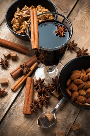 mulled: A glass of hot mulled wine, spices, cinnamon, star anise, brown sugar and nuts on a wooden board
