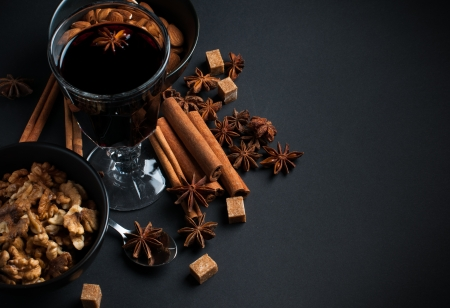 A glass of hot mulled wine, spices, cinnamon, star anise, brown sugar and nuts on a black background in studio Stock Photo