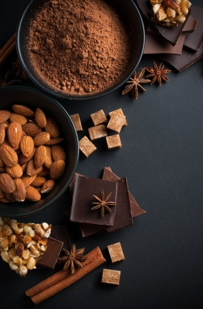 Black and milk chocolate, cocoa powder, nuts, sweets, spices and brown sugar on a black background, food concept photo