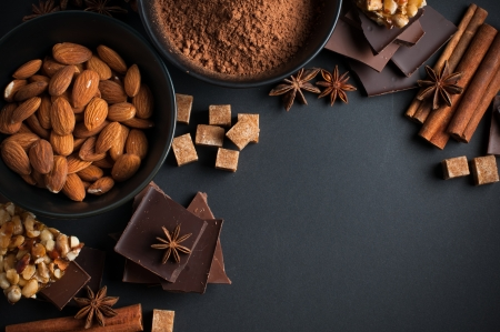 chocolate background: Black and milk chocolate, cocoa powder, nuts, sweets, spices and brown sugar on a black background, food concept