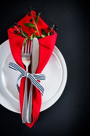 Autumn table setting with wild grapes, dried herbs and berries in a napkin with a ribbon, plate, fork and knife on a black background