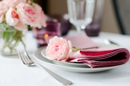 Beautiful festive table setting with roses, candles, shiny new cutlery and napkins on a white tablecloth.