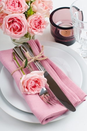 wedding table decor: Beautiful festive table setting with roses, candles, shiny new cutlery and napkins on a white tablecloth.