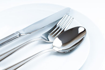 Shiny new cutlery, silverware close-up on white background Stock Photo