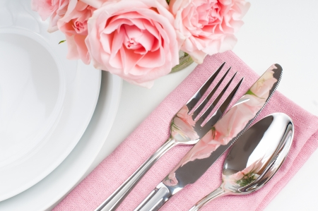 silver cutlery: Shiny new cutlery, silverware and a napkin with flowers, close-up on white background