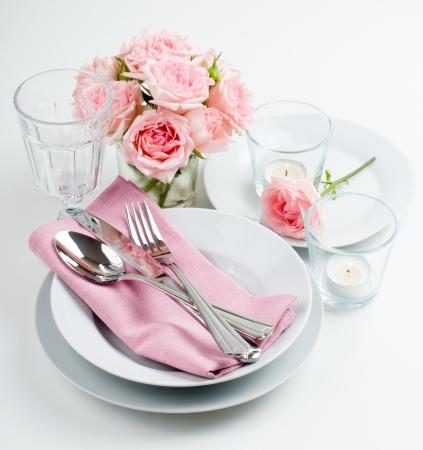 Luxueuze lijst die met roze rozen, kaarsen en glanzende nieuwe bestek op een witte achtergrond, geïsoleerd Stockfoto