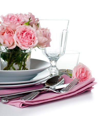 Luxurious table setting with pink roses, candles and shiny new cutlery on a white background, isolated photo