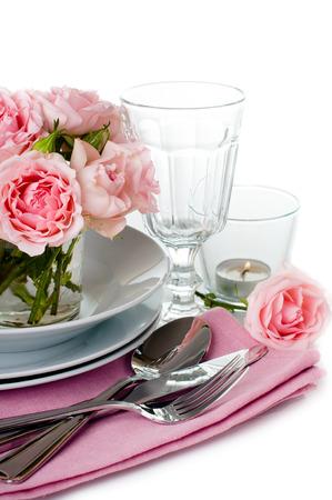 Luxuriöse gedeckten Tisch mit rosa Rosen, Kerzen und glänzende neue Besteck auf einem weißen Hintergrund, isoliert