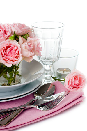 Luxurious table setting with pink roses, candles and shiny new cutlery on a white background, isolated
