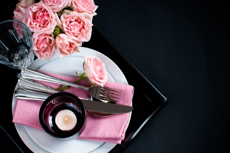 Luxury festive table setting with pink roses, candles and shiny new cutlery on black background isolated photo