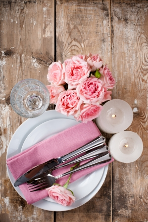 Vintage festive table setting with pink roses, candles and cutlery on an old wooden board photo