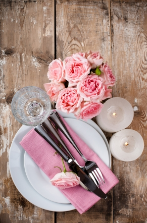 wedding table setting: Vintage festive table setting with pink roses, candles and cutlery on an old wooden board