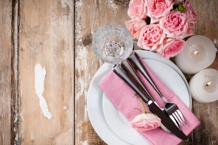 Weinlese festlich gedeckten Tisch mit rosa Rosen, Kerzen und Besteck auf einem alten Holzbrett