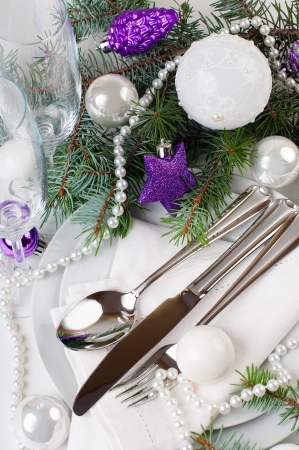 Festive Christmas table setting, table decoration in purple tones, with fir branches, Christmas balls on a white background, isolated photo