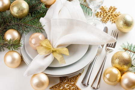 Festive Christmas table setting, table decorations in gold tones, with fir branches, baubles, decorations. Stock Photo
