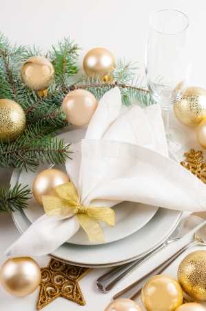 Festive Christmas table setting, table decorations in gold tones, with fir branches, baubles, decorations. 版權商用圖片