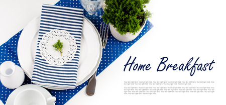 Table setting for breakfast with napkins, cups, plates in navy blue tones on a white background isolated photo