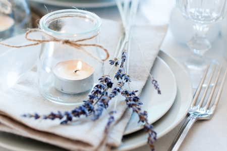 table set: Dining table setting at Provence style, with candles, lavender, vintage crockery and cutlery, closeup  Stock Photo