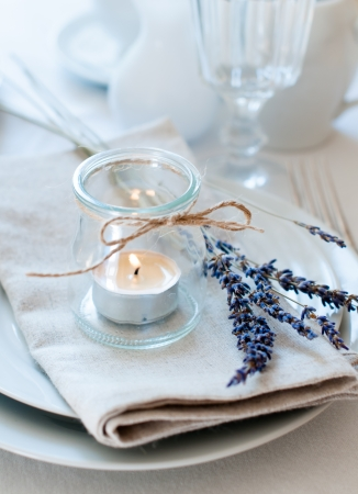 Dining table setting at Provence style, with candles, lavender, vintage crockery and cutlery, closeup  Stock Photo