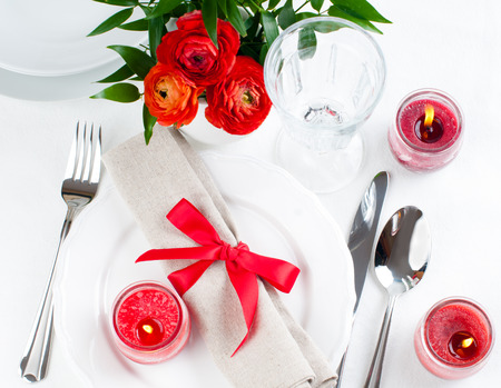 Festive dining table setting with red flowers, candles and ribbons in white tones photo
