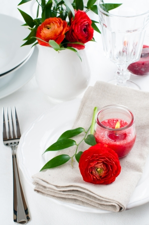 Festive dining table setting with red buttercup flowers, candles, napkins and shiny new cutlery in white. photo
