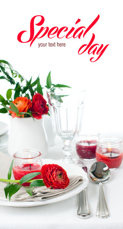 special events: Festive dining table setting with red buttercup flowers, candles, napkins and shiny new cutlery in white