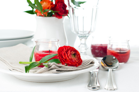 Festive dining table setting with red buttercup flowers, candles, napkins and shiny new cutlery in white  photo