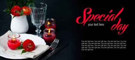 anniversary sexy: Festive dining table setting with red buttercup flowers, candles, napkins and shiny new cutlery on a black background