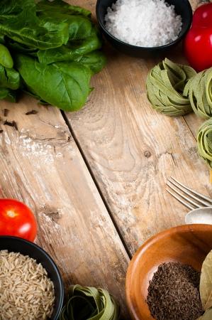 farme: Sfondo di cibo, verdure fresche, pomodori, peperoni, spinaci verde, sale, riso, pasta, spezie e utensili da cucina su una tavola di legno, close-up