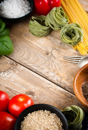 Food background, fresh vegetables, tomatoes, peppers, green spinach, salt, rice, pasta, spices and kitchen utensils on a wooden board, close-up photo