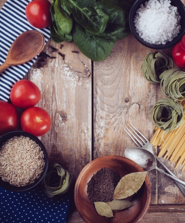farme: Sfondo di cibo, verdure fresche, pomodori, peperoni, spinaci verde, sale, riso, pasta, spezie e utensili da cucina su una tavola di legno, close-up, stile vintage