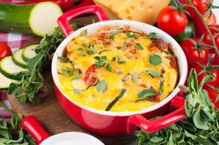casserole: Vegetable casserole in a red pot with cheese, zucchini, cherry tomatoes, oregano and cream sauce on a white background, Italian cuisine