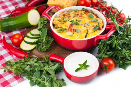 lasagna: Vegetable casserole in a red pot with cheese, zucchini, cherry tomatoes, oregano and cream sauce on a white background, Italian cuisine
