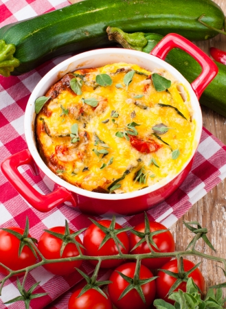 Vegetable casserole in a red pot with cheese, zucchini, cherry tomatoes, oregano and cream sauce on a wooden board, home cooking