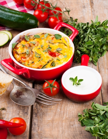 Vegetable casserole in a red pot with cheese, zucchini, cherry tomatoes, oregano and cream sauce on a wooden board, home cooking photo